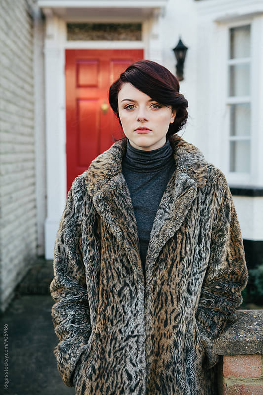 Young woman in the street wearing fake fur coat by kkgas for Stocksy United