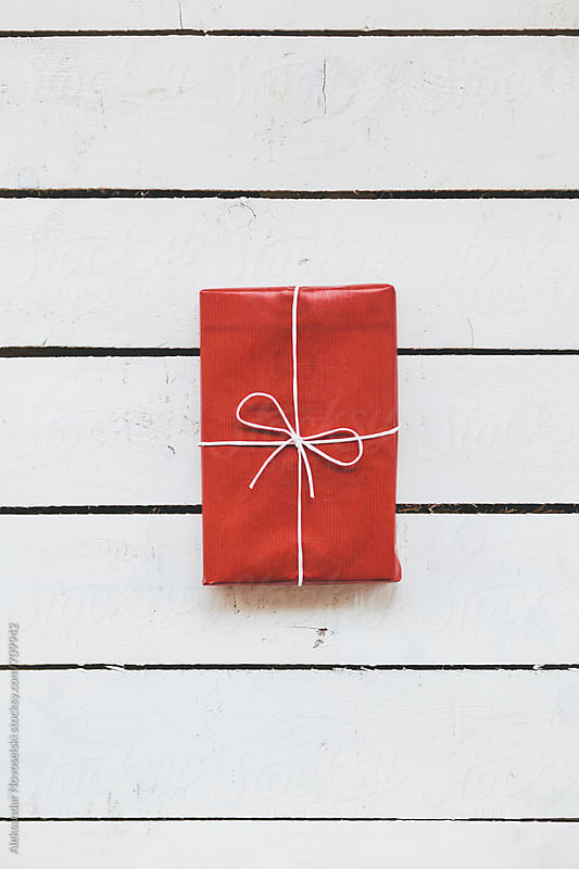 Christmas presents wrapped in red paper on a white wooden background by Aleksandar Novoselski for Stocksy United