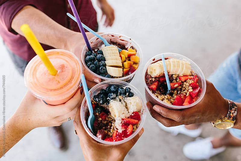 A group of friends holding up their acai bowls together  by Kristen Curette Hines for Stocksy United