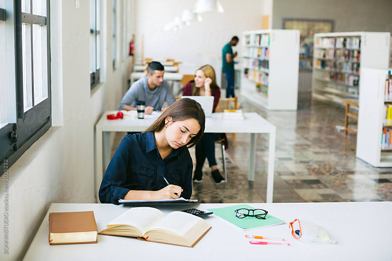 University woman studying in a library. by BONNINSTUDIO for Stocksy United