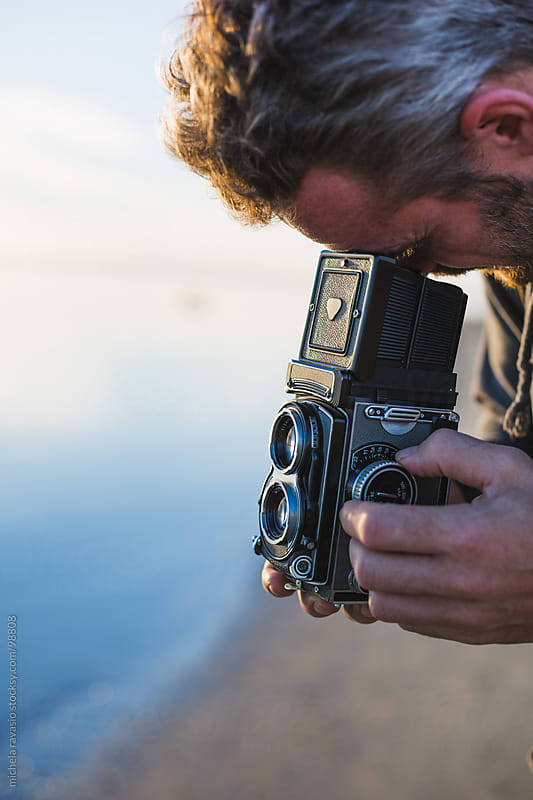 Man taking a photo with an old camera by michela ravasio for Stocksy United