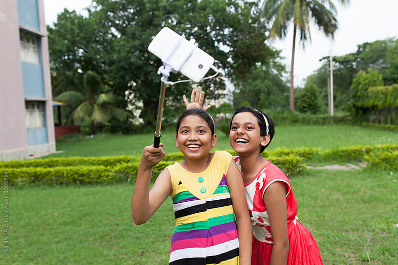 Teenage girls taking shots with selfie stand and smartphone by PARTHA PAL for Stocksy United