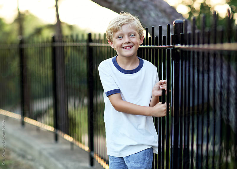 smiling boy beside a fence by Kelly Knox for Stocksy United