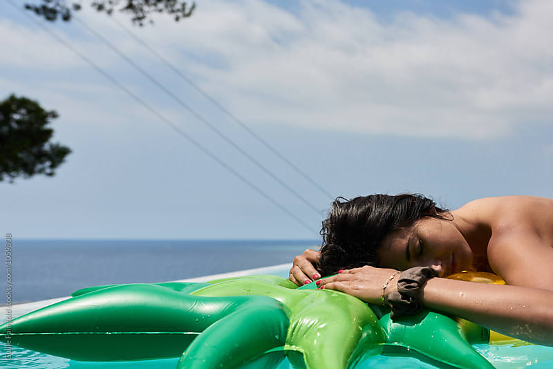 Relaxed brunette with eyes closed on inflatable at pool by Guille Faingold for Stocksy United