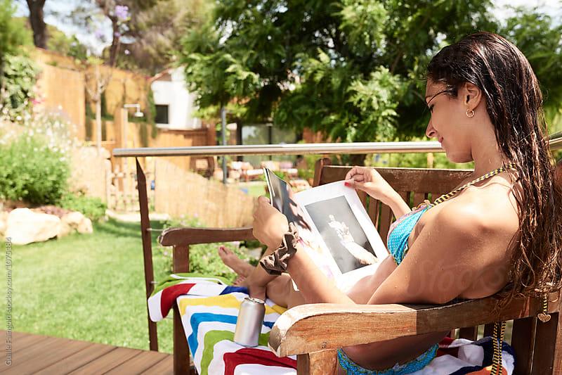 Wet-haired brunette reading magazine on bench in garden by Guille Faingold for Stocksy United