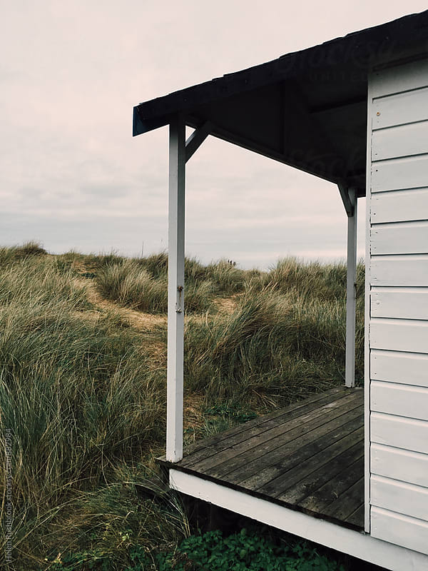 Sand dunes framed by the porch of a beach hut. by Helen Rushbrook for Stocksy United