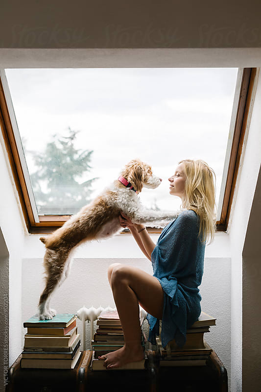 Beautiful Woman Playing with Her Dog at Home by Victor Torres for Stocksy United