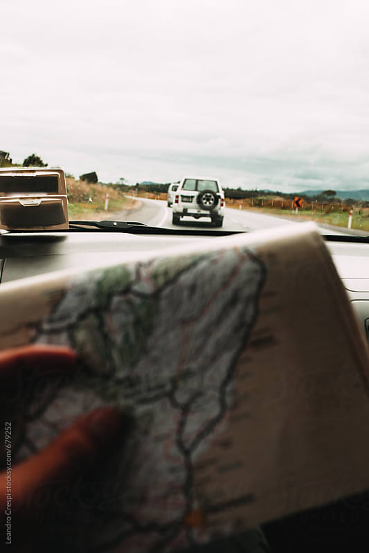 Displaying a map on a road trip by Leandro Crespi for Stocksy United
