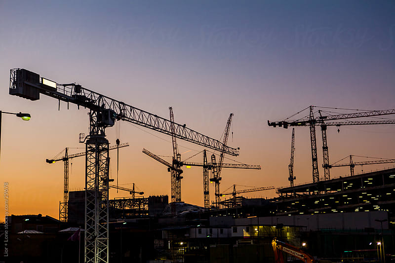 Cranes over construction site at sunset by Lior + Lone for Stocksy United