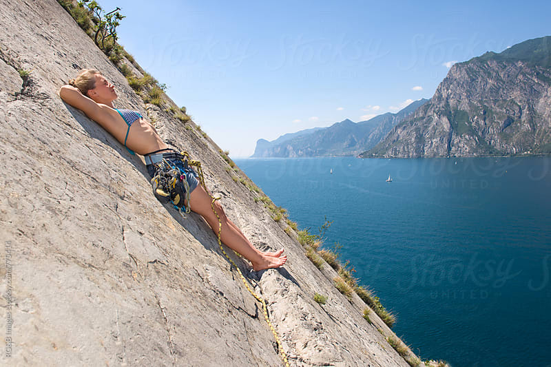 Rock climber relaxing on a rock ledge above the lake by RG&B Images for Stocksy United