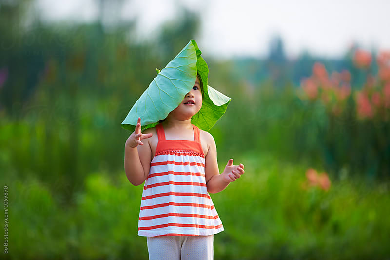 lovely little asian girl playing with lotus leaf outdoor by cuiyan Liu for Stocksy United