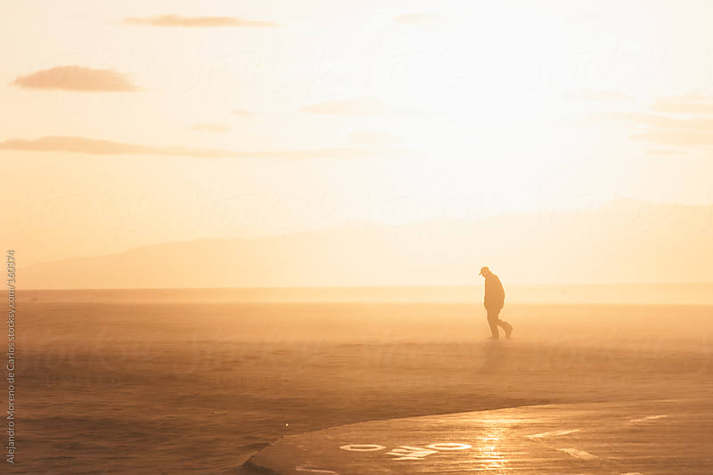 Man walking on the beach at sunset, silhouette by Alejandro Moreno de Carlos for Stocksy United