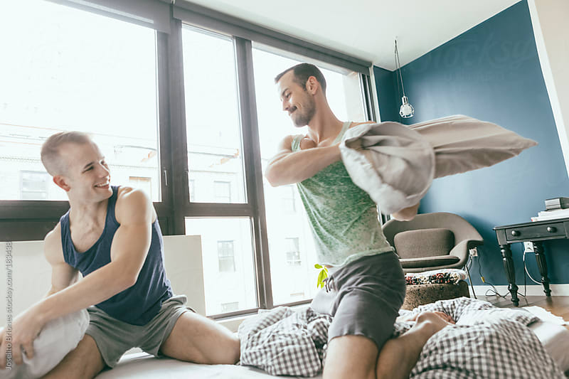 Playful Gay Male Jock Couple having Pillow Fight at Home by Joselito Briones for Stocksy United