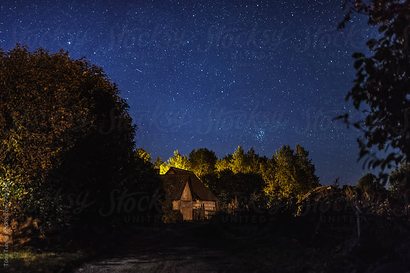 Starry sky over a small farmhouse by Tõnu Tunnel for Stocksy United