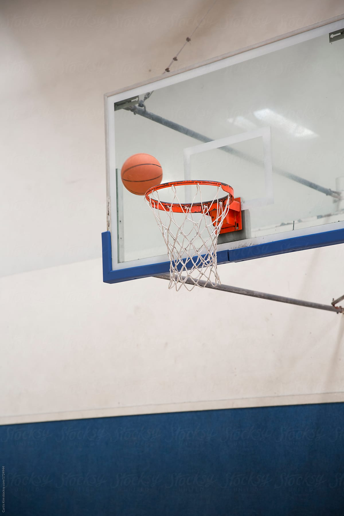 basketball going into basket in an indoor gym stocksy united