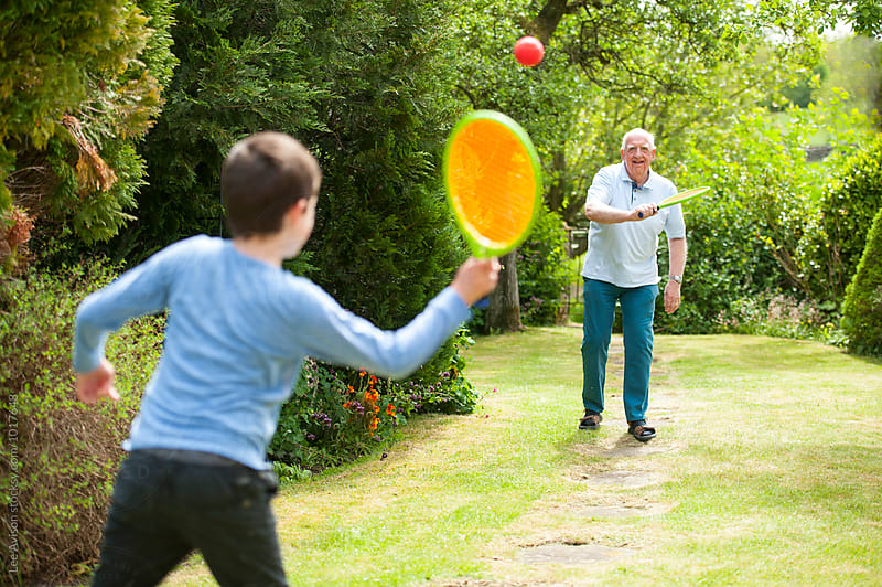 grandfather and grandson playing tennis by Lee Avison for Stocksy United