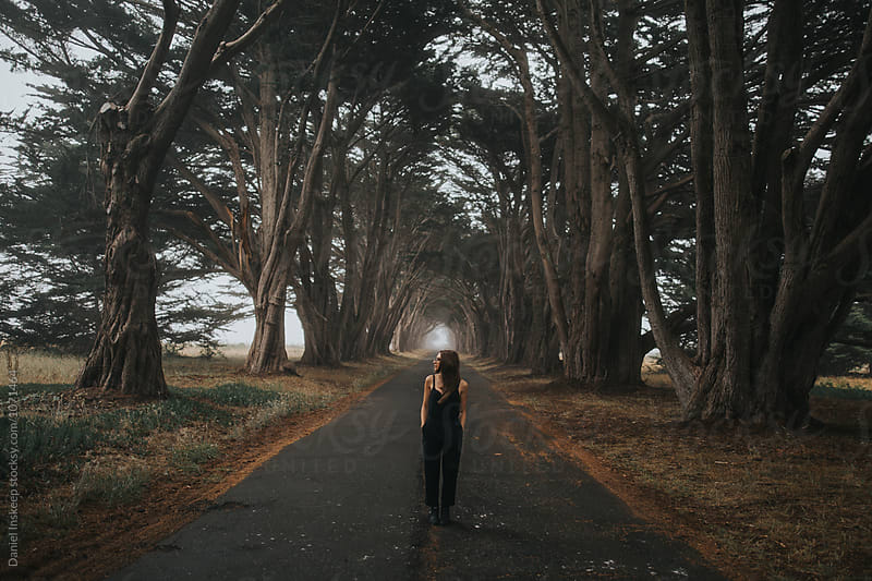 Woman Looking Away in Cypress Tree Tunnel by Daniel Inskeep for Stocksy United