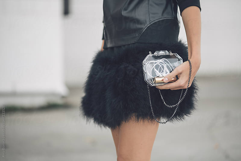 A closeup of a woman holding a transparent purse containing headphones and lipstick by Ania Boniecka for Stocksy United