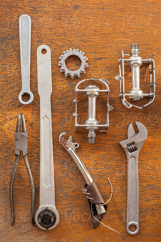 Bicycle Spare Parts and Tools on a Wooden Background by Mosuno for Stocksy United