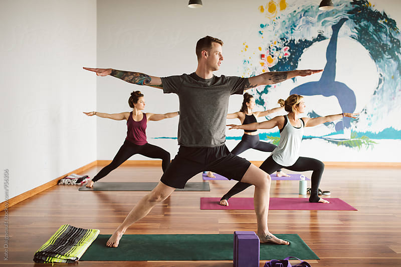 Group of young adults in yoga class by Kate Daigneault for Stocksy United