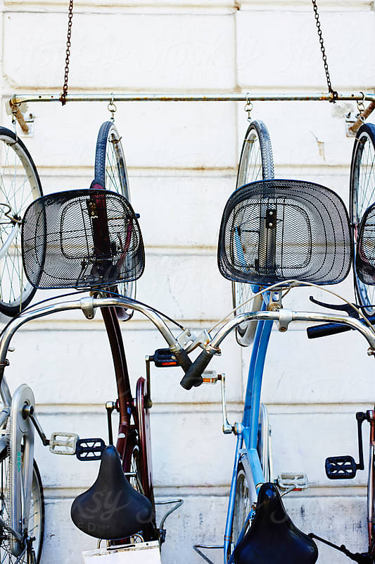 bikes hanging on white outside wall by Atakan-Erkut Uzun for Stocksy United