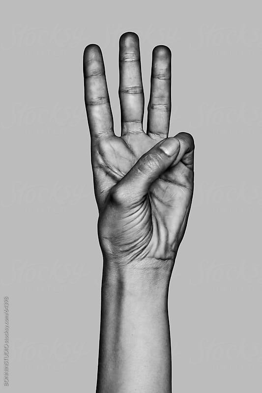 Hand making the number three sign. Black and white photo. by BONNINSTUDIO for Stocksy United