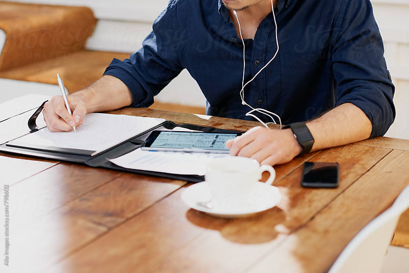 Businessman working at desk with coffee and digital tablet by Aila Images for Stocksy United