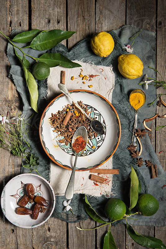 Lemons, limes and several species on a hand-painted spanish ceramics on a worn wood surface  by Marta Muñoz-Calero Calderon for Stocksy United