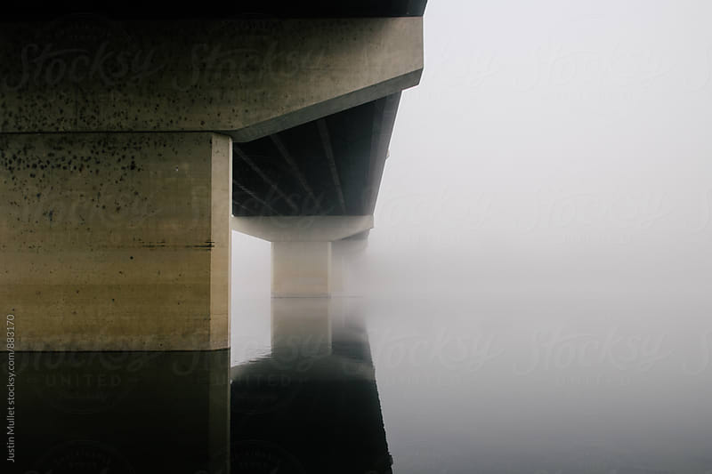 Calm water underneath a concrete bridge surrounded in thick fog by Justin Mullet for Stocksy United