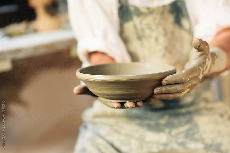 Close-up on potters hands making clay pottery by Adrian Cotiga for Stocksy United