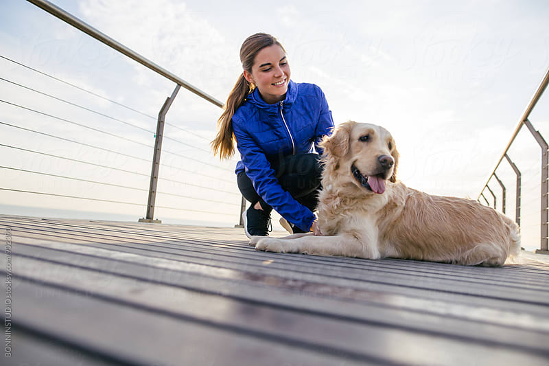 Runner woman caressing her dog after workout. by BONNINSTUDIO for Stocksy United