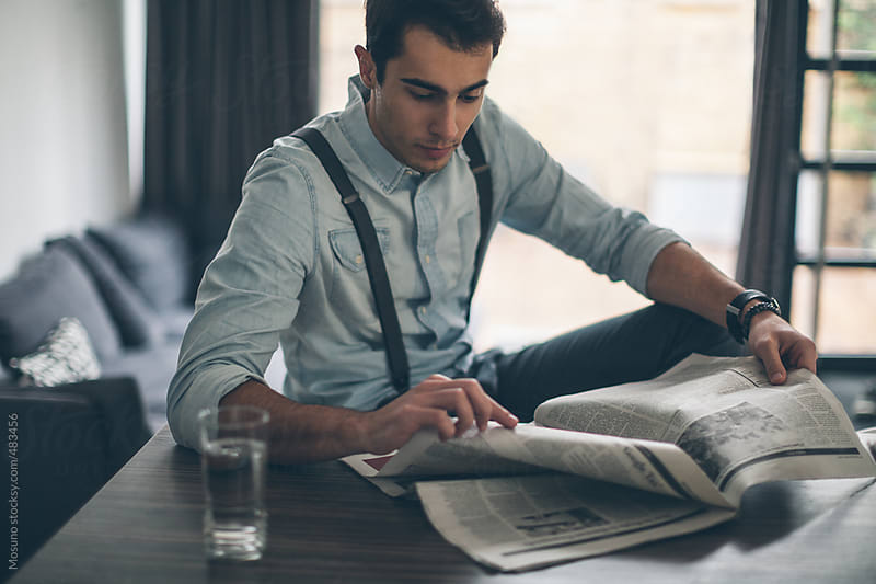 Young Man Reading Morning Newspaper by Mosuno for Stocksy United