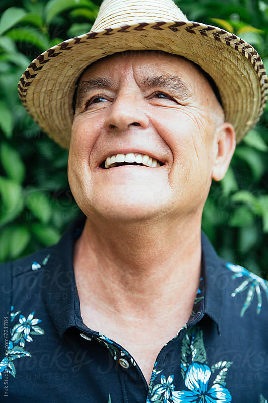 Stylish senior man portrait laughing wearing a straw hat by Inuk Studio for Stocksy United