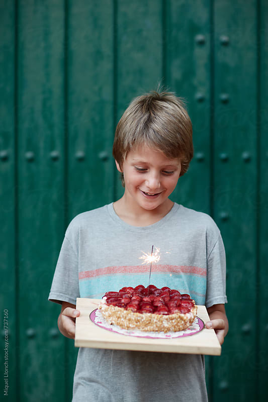 Happy boy with birthday cake and sparkle by Miquel Llonch for Stocksy United