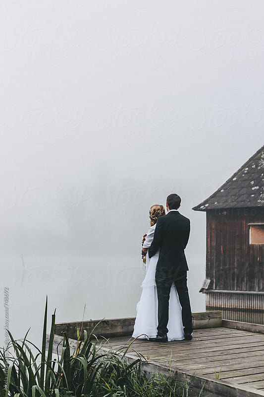 bridal couple on a jetty in foggy landscape by Leander Nardin for Stocksy United