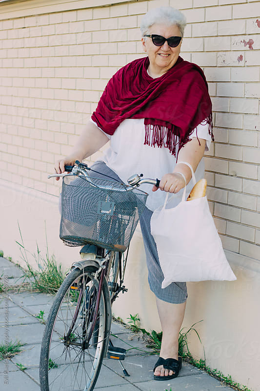 Portrait of senior woman with bike and sunglasses by Evil Pixels  Photography for Stocksy United