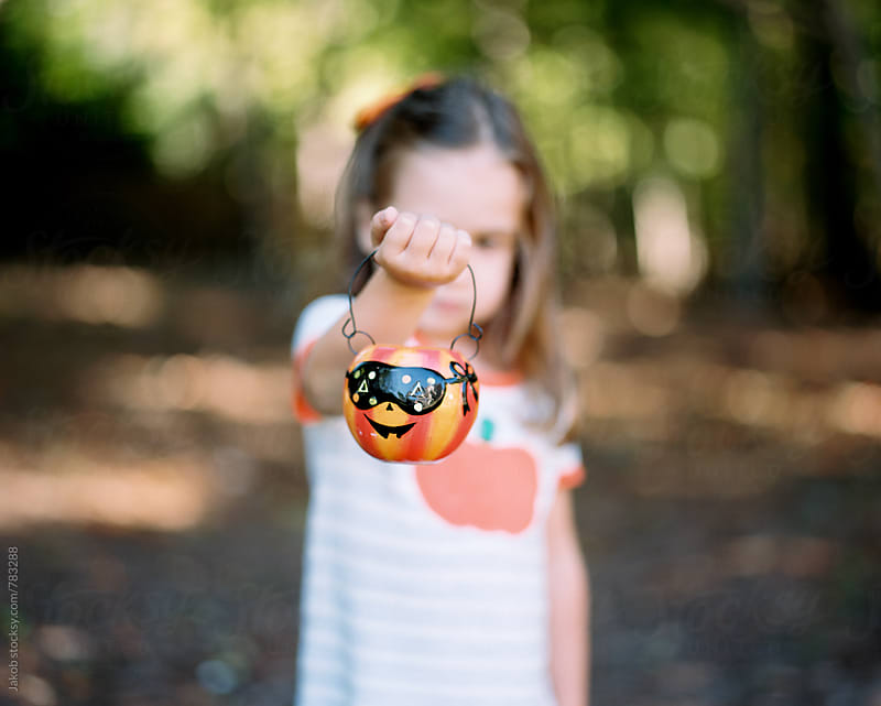 Cute young girl holding up a halloween pumpkin by Jakob for Stocksy United