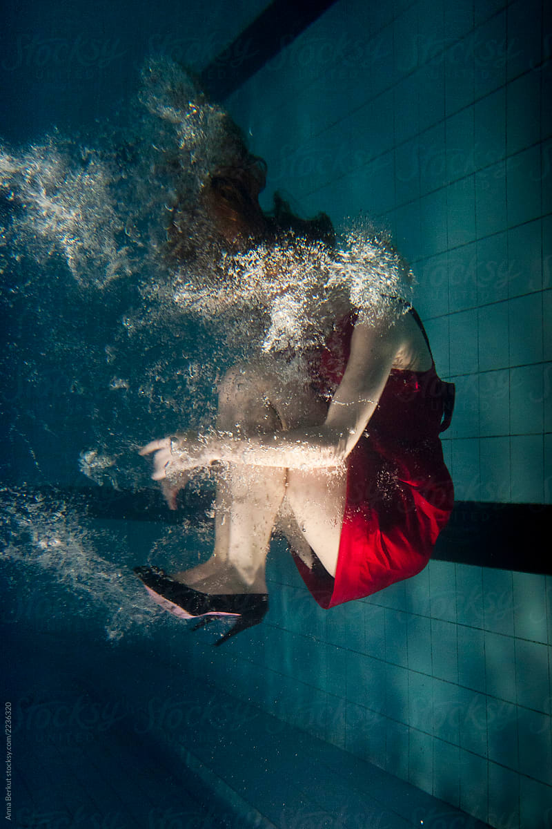 woman in red dress underwater wearing fashion shoes with