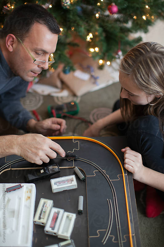 Father and daughter in front of the Christmas tree building a mini train set by Carolyn Lagattuta for Stocksy United