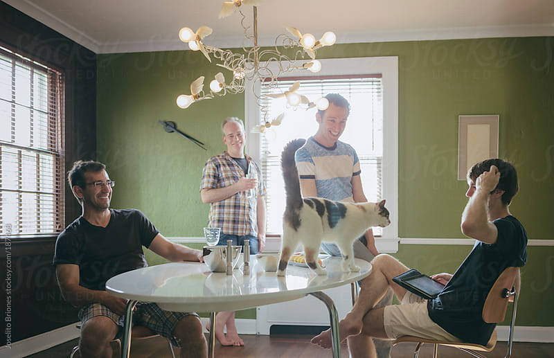 Group of Gay Friends Having Drinks and Chatting in a Dining Room on a Weekend Afternoon by Joselito Briones for Stocksy United