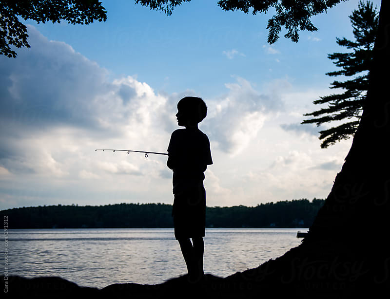 Silhouette of a boy fishing on a lake at sunset by Cara Dolan for Stocksy United