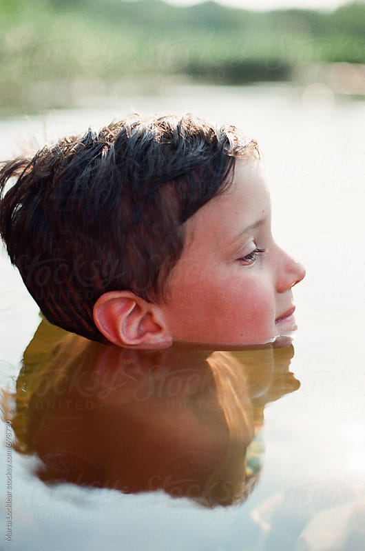 Head of a boy popping out of the water by Marta Locklear for Stocksy United