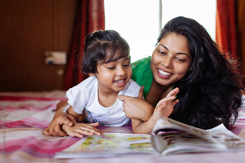 Little girl sharing a cheerful moment with her mother while studying by Saptak Ganguly for Stocksy United