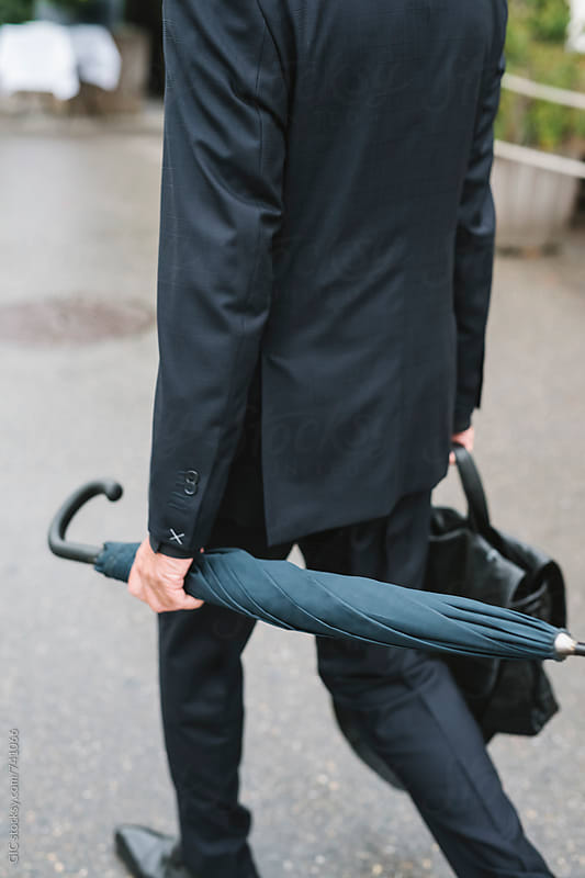 Man walking holding an umbrella by Simone Becchetti for Stocksy United