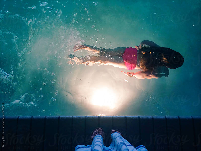 A young girl swims across a pool at night in front of the light. by Kelsey Gerhard for Stocksy United