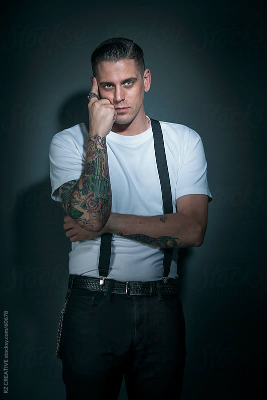 Portrait of a man wearing a white t-shirt with suspenders looking at camera. by Robert Zaleski for Stocksy United