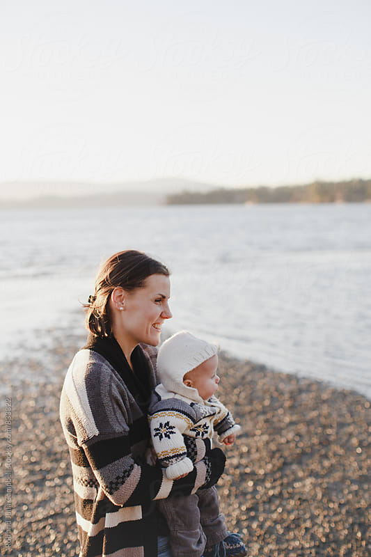 Young smiling mother holding baby outside at the beach by Rob and Julia Campbell for Stocksy United