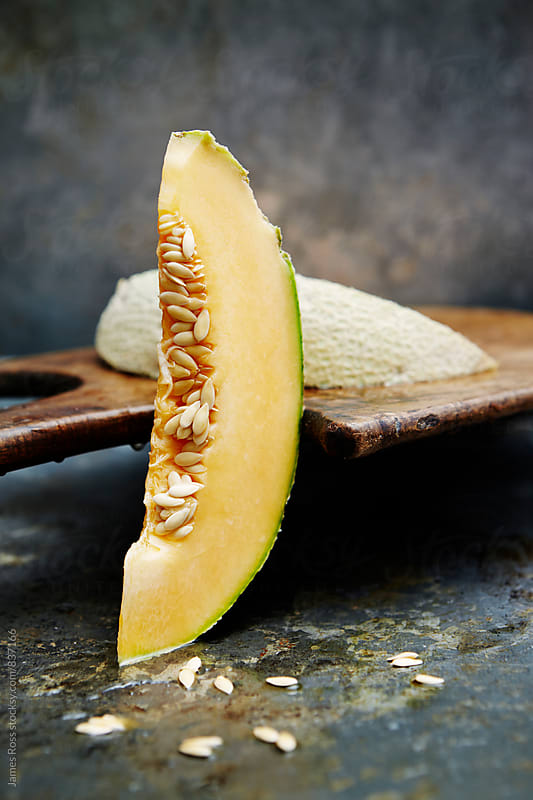 Two slices of cantaloupe melon by James Ross for Stocksy United