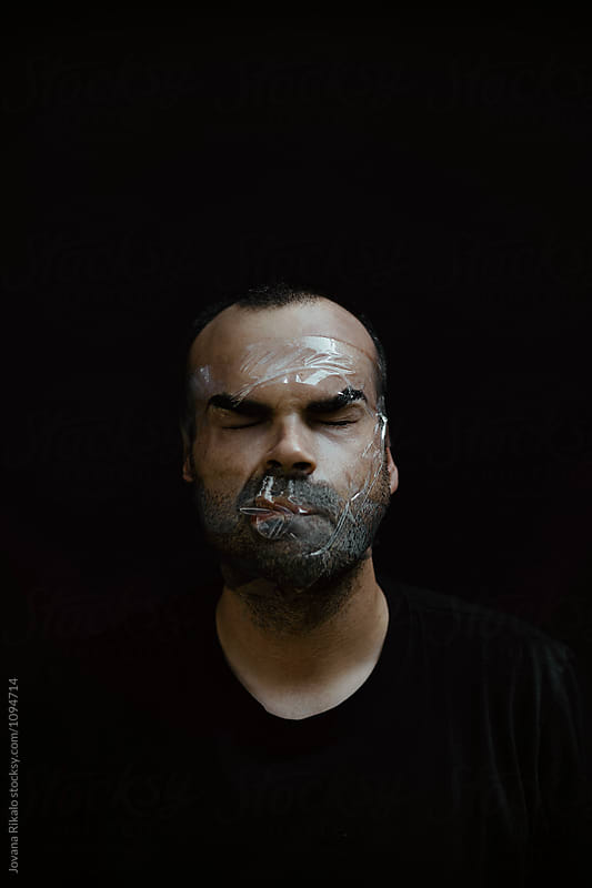 Artistic portrait of a man with face covered with tape by Jovana Rikalo for Stocksy United