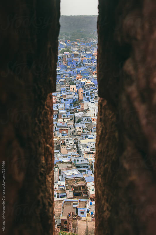 Blue houses and buildings in Jodhpur, India, seen through a hole by Alejandro Moreno de Carlos for Stocksy United